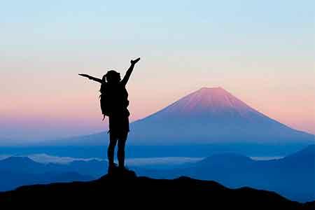 富士山を目の前にして万歳をする人